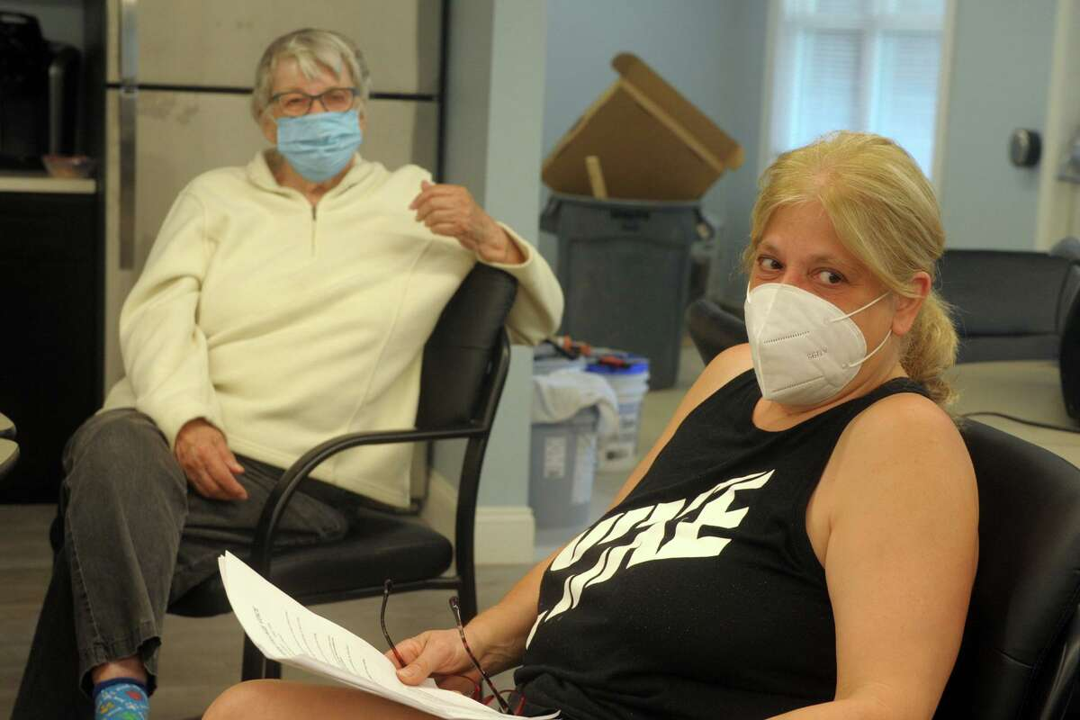 Residents Joan Sierra, left, and Karen Andalora keep cool in the recently renovated community room at Stern Village, in Trumbull, Conn. Aug. 6, 2020. Stern Village remained without power on Thursday afternoon.