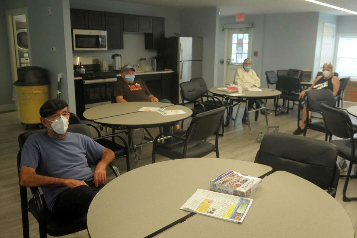 Residents keep cool in the recently renovated community room at Stern Village, in Trumbull, Conn. Aug. 6, 2020. Stern Village remained without power on Thursday afternoon.