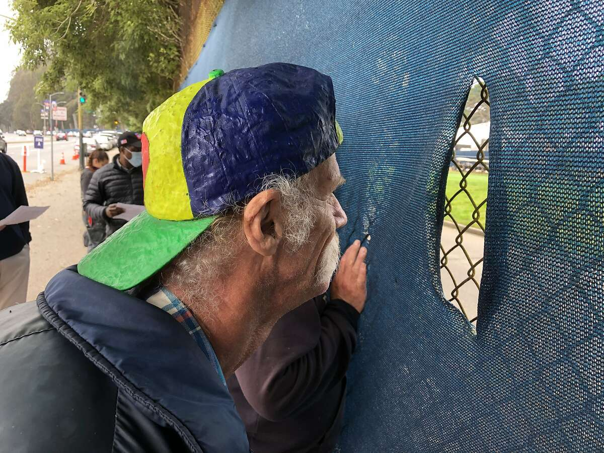 Jim McAfee peers through the fence of Harding Park on Lake Merced Boulevard to watch the first round of the PGA Championship on Thursday in San Francisco. Spectators were not allowed inside the golf course due to the coronavirus pandemic.