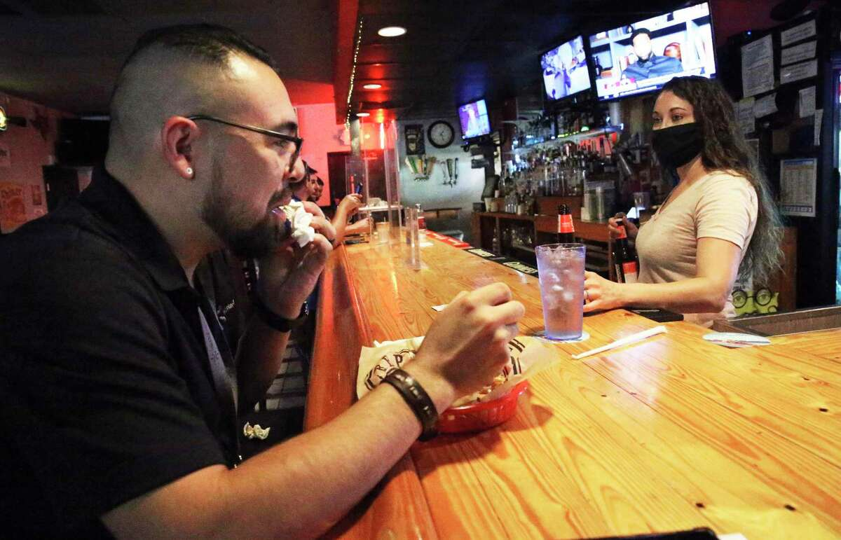 Alejandro Ramirez Jr., finishing his chicken wings, chats with bartender Lisa Krudwig as customers enjoy a lunchtime break at Charlie Brown's Neighborhood Bar & Grill.