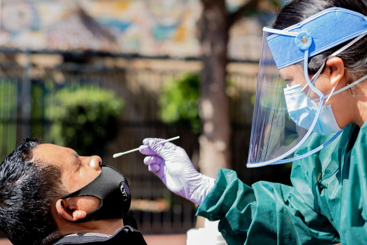 Nurse Marla Ayala (right) administers a COVID-19 test outside to a patient (name not given) of outside the 24th Street Bart station in San Francisco's Mission District in San Francisco, Calif. on Friday, July 31, 2020. UCSF will be offering testing Wednesday and Friday from 7 a.m. to 6 p.m. for the next three weeks