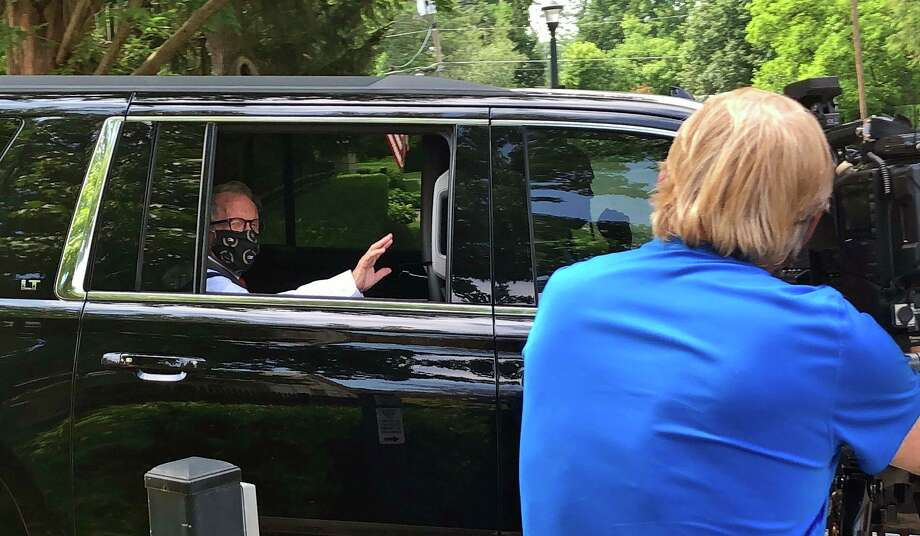 Ohio Gov. Mike DeWine waves to journalists gathered outside his official residence as he leaves for his family home in Greene County where he planned to talk about his positive coronavirus test, on Thursday, August 6, 2020, in Bexley, Ohio. The Republican DeWine, an early advocate among Republicans of wearing masks and other pandemic precautions, tested positive Thursday for the coronavirus just ahead of a planned meeting with President Donald Trump. (AP Photo/Andrew Welsh-Huggins) / Copyright 2020 The Associated Press. All rights reserved.