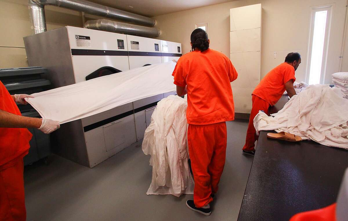 Detainees at the Mesa Verde Detention Facility are paid to work in the facility. These men work in the laundry room to earn a little money.