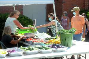 Trudy Lisky and Joey Moncheski, left, from Grassy Hill Farm, in Orange, assist customers.