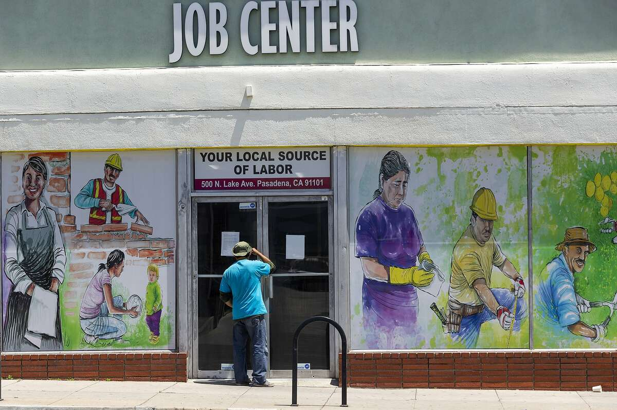 FILE - In this May 7, 2020, file photo, a person looks inside the closed doors of the Pasadena Community Job Center in Pasadena, Calif., during the coronavirus outbreak. California lawmakers had harsh words Thursday, July 30, 2020, for the state agency that pays out unemployment, accusing its leaders of failing Californians who are waiting weeks or even months to receive their benefits. (AP Photo/Damian Dovarganes, File)