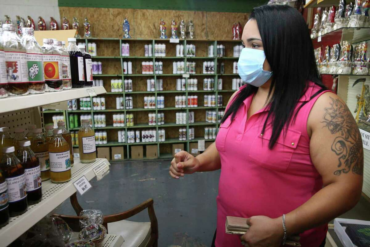 Megan Fernandez, 32, of Poteet, browses items at Papa Jim's Botanica. More and more people are turning to botanicas for help in coping with the COVID-19 epidemic, such as getting or keeping a job to herbal teas for breathing problems.