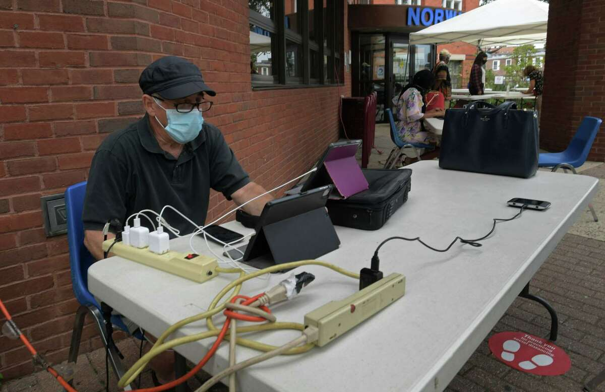 Local residents crowd the outside of the Norwalk Public Library utilizing the WIFI and power outlets Thursday, August 6, 2020, in Norwalk, Conn. Residents continue to struggle with power outages following the tropical storm Tuesday.