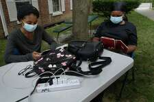 Local residents including Deonna and Marie Joyner crowd the outside of the Norwalk Public Library utilizing the WIFI and power outlets Thursday, August 6, 2020, in Norwalk, Conn. Residents continue to struggle with power outages following the tropical storm Tuesday.