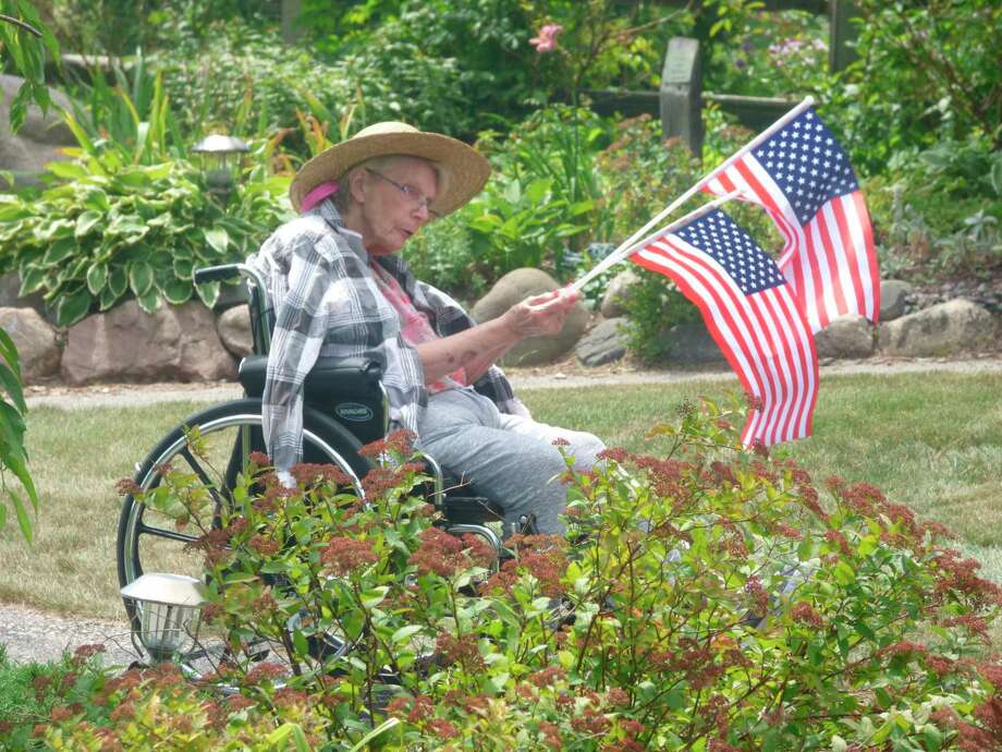 Some residents of the Manistee County Medical Care Facility came out to witness the dedication of a new flag in the facility's award-winning garden. (Scott Fraley/News Advocate)