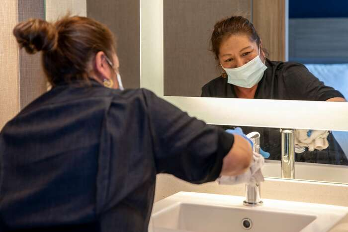 A housekeeper works to clean the bathroom of a room at an undisclosed hotel in the Bay Area, Calif. Thursday, August 6, 2020. The race is on to get in on the first round of applications for $100 million in Project Homekey funding to covert hotels in the Bay Area into permanent homeless housing such as this one. The first deadline is August 13, 2020.