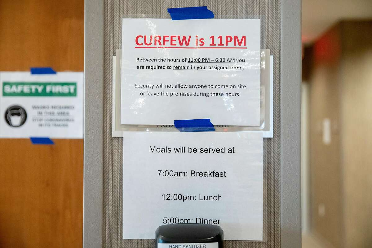 Signs remind visitors of meal times, curfew and mask requirements at an undisclosed hotel housing the homeless during the COVID-19 pandemic in the Bay Area, Calif. Thursday, August 6, 2020. The race is on to get in on the first round of applications for $100 million in Project Homekey funding to covert hotels in the Bay Area into permanent homeless housing such as this one. The first deadline is August 13, 2020.