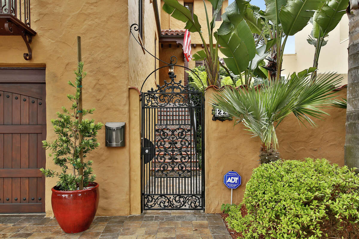 Period details abound: from the outside, we see the home's warm honey-toned stucco, its lace iron gate and balcony, plus lush Mediterranean foliage.