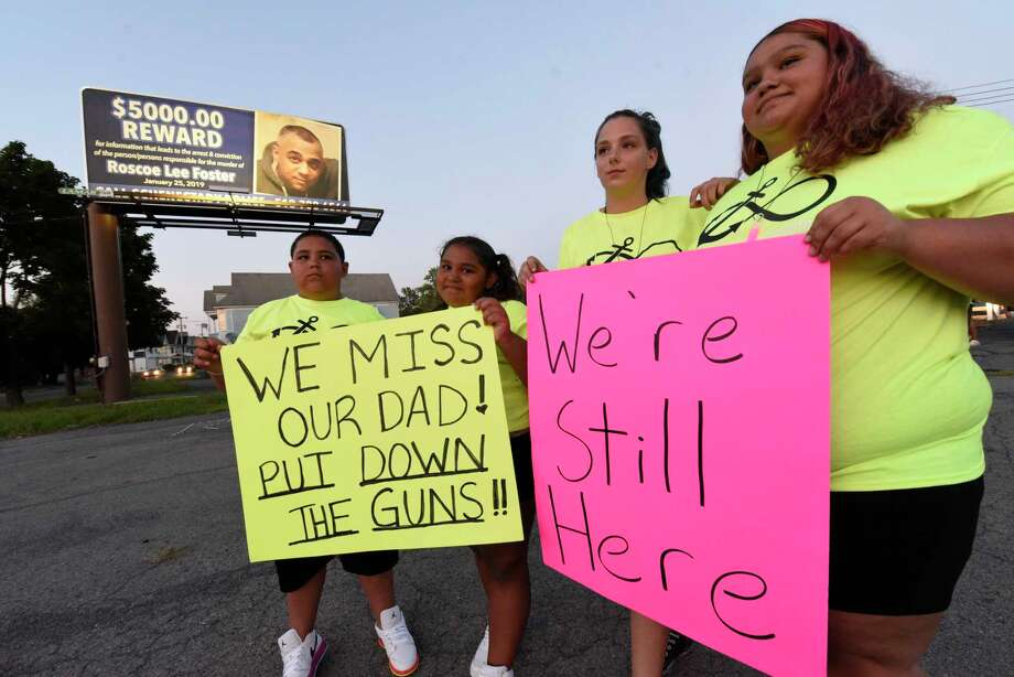 Roscoe Foster's children, from left, Jasiah Foster, 10, Linda Foster, 9, Ashley Parker 21 and Savannah Foster, 14, hold signs they made as people attend a candlelight vigil at the intersection of State Street and Brandywine Avenue to draw attention to the unsolved 2019 shooting death of Roscoe Foster on Thursday, Aug. 6, 2020 in Schenectady, N.Y. A reward billboard is seen in the background. (Lori Van Buren/Times Union) Photo: Lori Van Buren, Albany Times Union / 20049735A