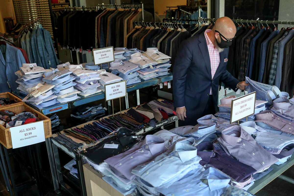 """Mark Smelser shops for shirts at a Tootsies and Norton Ditto pop-up sale Thursday, Aug. 6, 2020, in Houston. """"A good sale, that'll always get you out,"""" he said."""