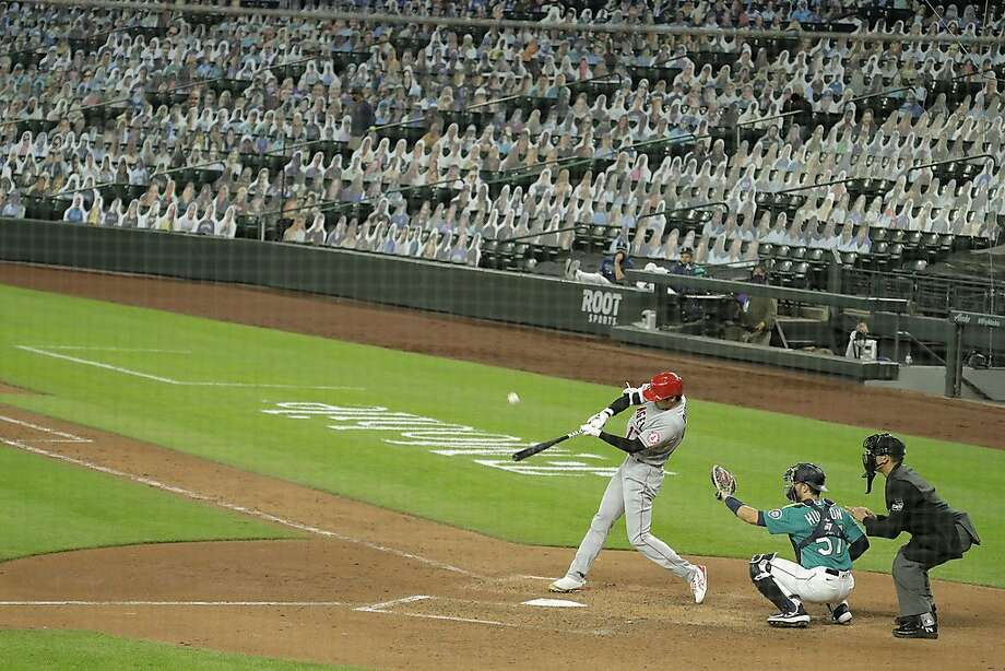With photos of fans filling the seats at Safeco Field, Los Angeles Angels' Shohei Ohtani flies out to center field to end the top the seventh inning of a baseball game against the Seattle Mariners, Thursday, Aug. 6, 2020, in Seattle. (AP Photo/Ted S. Warren) Photo: Ted S. Warren / Associated Press