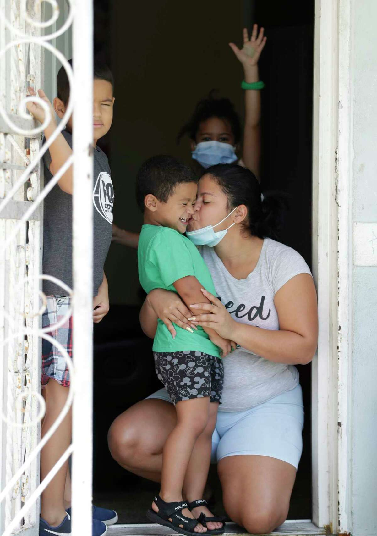 Greyla Javier, right, kisses her son Erick Benavides, 3, who is visually impaired, as her other son Abdiel, left, 7, who is also visually impaired, and her daughter Solimar, rear, 5, look on as they receive food, Thursday, Aug. 6, 2020, at their home in Miami. Miami Lighthouse for the Blind and Visually Impaired provided the meals to needy families with blind or visually impaired children who have been economically affected by the COVID-19 pandemic. Miami Lighthouse started the Family Security Fund Campaign and has been spending an average of $3,500 a week to help numerous local families who are experiencing food insecurities. (AP Photo/Wilfredo Lee)