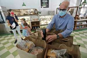 Steven Perricone, right, seals up bags of meals, Thursday, Aug. 6, 2020, at his Perricone's Marketplace & Cafe restaurant in Miami. Miami Lighthouse for the Blind and Visually Impaired provided the meals to needy families with blind or visually impaired children who have been economically affected by the COVID-19 pandemic. Miami Lighthouse started the Family Security Fund Campaign and has been spending an average of $3,500 a week to help numerous local families who are experiencing food insecurities. (AP Photo/Wilfredo Lee)