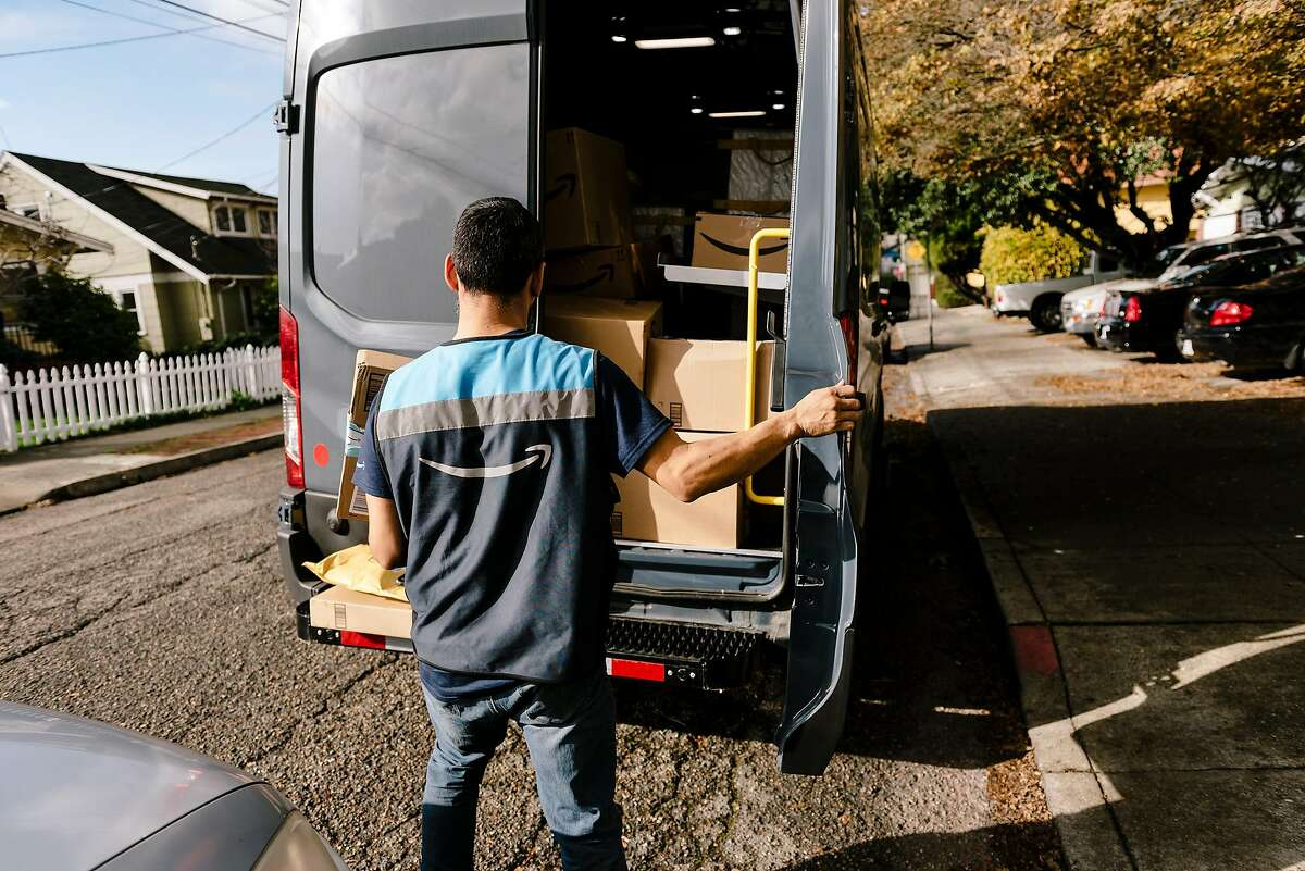 An Amazon driver sifts through items in his van while making deliveries to residents in Oakland, California, Thursday, December 19th, 2019.