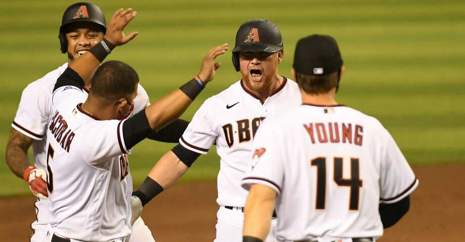 Kole Calhoun #56 of the Arizona Diamondbacks celebrates with Eduardo Escobar #5, Andy Young #14 an Ketel Marte #4 after hitting a walk off two run single during the ninth inning for a 5-4 win against the Houston Astros at Chase Field on August 06, 2020 in Phoenix, Arizona. (Photo by Norm Hall/Getty Images) Photo: Norm Hall/Getty Images / 2020 Getty Images