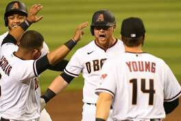 Kole Calhoun #56 of the Arizona Diamondbacks celebrates with Eduardo Escobar #5, Andy Young #14 an Ketel Marte #4 after hitting a walk off two run single during the ninth inning for a 5-4 win against the Houston Astros at Chase Field on August 06, 2020 in Phoenix, Arizona. (Photo by Norm Hall/Getty Images)