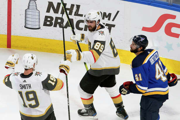 The Blues' Robert Bortuzzo (right) looks on as the Golden Knights' Reilly Smith (19) and Alex Tuch celebrate a goal during the second period Thursday in Edmonton, Alberta.