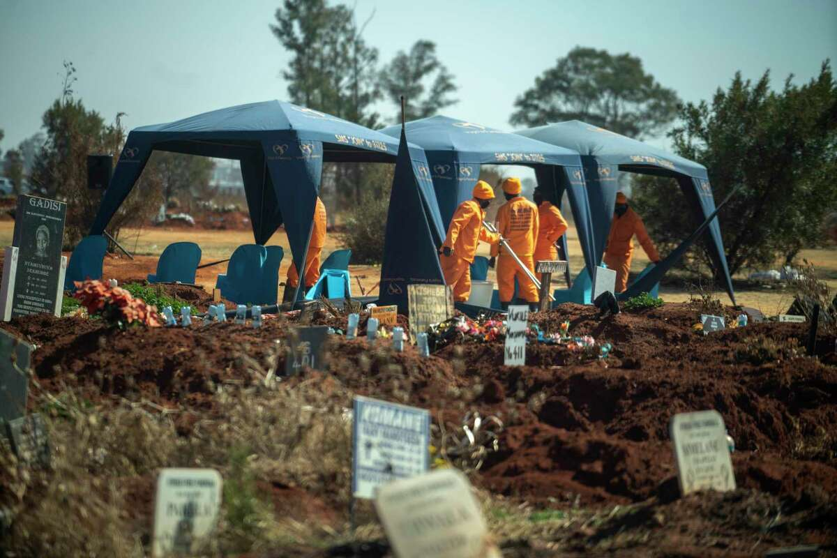 Workers prepare for a burial at the Olifantsveil Cemetery outside Johannesburg, South Africa, Thursday Aug. 6, 2020. The frequency of burials in South Africa has significantly increased during the coronavirus pandemic, as the country became one of the top five worst-hit nations. New infection numbers around the world are a reminder that a return to normal life is still far off. (AP Photo/Jerome Delay)