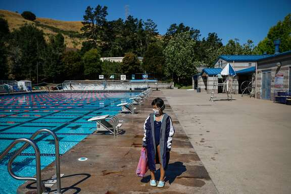 8-year-old student Alexa Wo waits for her older brother to get out of his swim camp before heading home at Soda Aquatic Center at Campolindo High School in Moraga, California on Thursday, July 2, 2020.