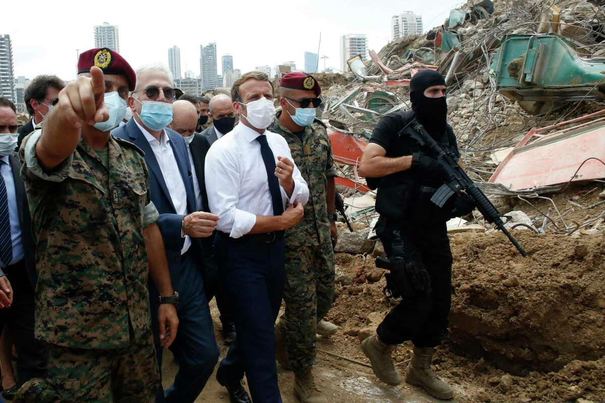 French President Emmanuel Macron, center, visits the devastated site of the explosion at the port of Beirut, Lebanon, Thursday Aug.6, 2020. French President Emmanuel Macron has arrived in Beirut to offer French support to Lebanon after the deadly port blast. (AP Photo/Thibault Camus, Pool)