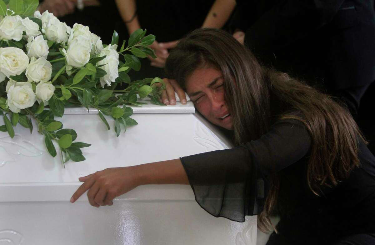 The sister of Nicole al-Helou, who was killed by the explosion Tuesday that hit the seaport of Beirut, mourns on her coffin during her funeral, in Sarba village, southern Lebanon, Thursday, Aug. 6, 2020. French President Emmanuel Macron said an independent, transparent investigation into the massive explosion in Beirut is