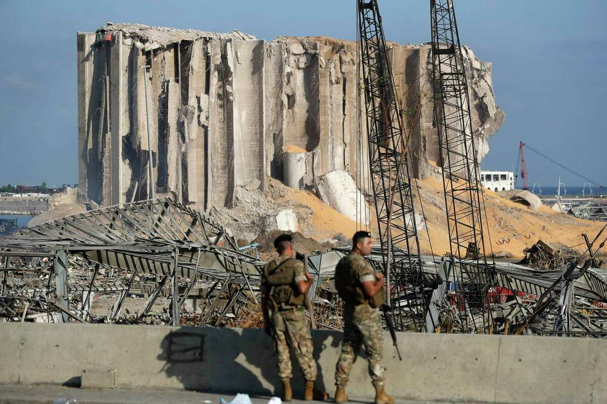 Lebanese army soldiers stand guard at the scene where an explosion hit on Tuesday the seaport of Beirut, Lebanon, Thursday, Aug. 6, 2020. Lebanese army bulldozers plowed through wreckage to reopen roads around Beirut's demolished port on Thursday as the government pledged to investigate the devastating explosion and placed port officials under house arrest. (AP Photo/Hussein Malla)