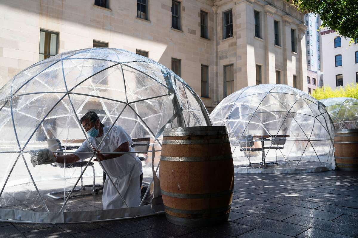 Toku Mekaru, 62, of San Francisco, disinfects a dining dome outside of Hashiri in San Francisco, Calif., on Thursday, August 6, 2020.