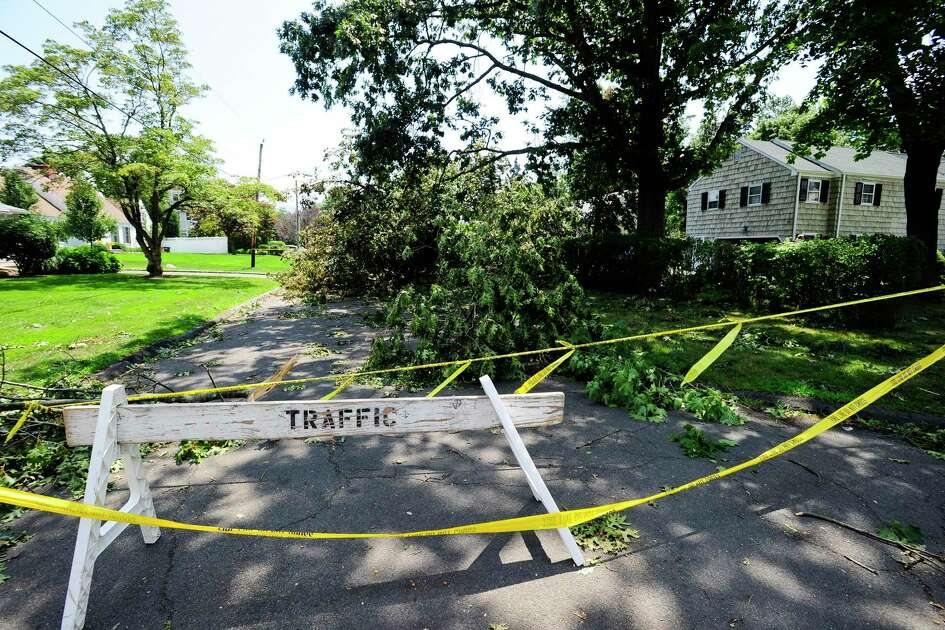 A traffic barrier and yellow caution tape close a section of Ocean Drive East in Stamford, Connecticut Shippan neighborhood on August 5, 2020. Residents in the area are without power following the aftermath of Tropical Storm Isaias.