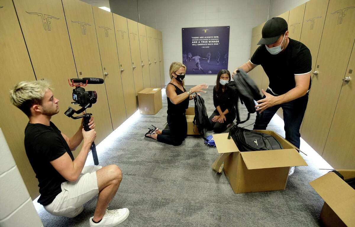 Tyler Spenncer films as Hollman's Tia Williams and Trey Stewart talk as they look over boxes of donated and branded backpacks with Varsity Brands' Julie Jackson, Vice President of Impact Design for Varsity in Dallas, as they continue to pack them for students and do final work to complete the locker room renovations at Hamshire - Fannett High School Wednesday, August 5. Varsity Brands, parent company of several other businesses that wortk with the school's programs, donated 332 backpacks for students, as well as branded rugs throughout the locker rooms.Jackson says they decided to join in the renovation project after being contacted by Hollman, and learning that over 50% of kids at the school lost their backpacks in flooding. Providing backpacks, small supply puches and area rugs emblazoned with the school's logo is