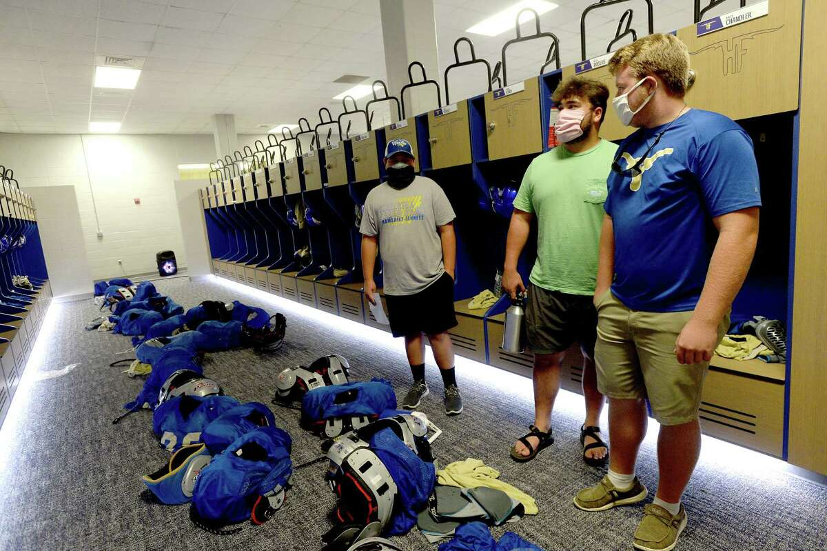 From left, Tre Romero, Blake Briggs and Vance Moore check out the finished locker room renovations at Hamshire - Fannett High School as they arrive for a practice after the work was completed Wednesday, August 5. Although the large pulic reveal party Hollman, Inc., had planned for the grand finale was canceled due to COVID-19, a small group of athletes were able to get a view of the final product Thursday during a private viewing. Hollman's Tia Williams says she and work crew have barely slept as they worked to complete the locker rooms in time for the start of the school year amid a global pandemic. They, like coaches and athletes, just hope that students are able to put the locker rooms to use as school begins amid uncertainty and ongoing case reports. Photo taken Wednesday, August 5, 2020 Kim Brent/The Enterprise