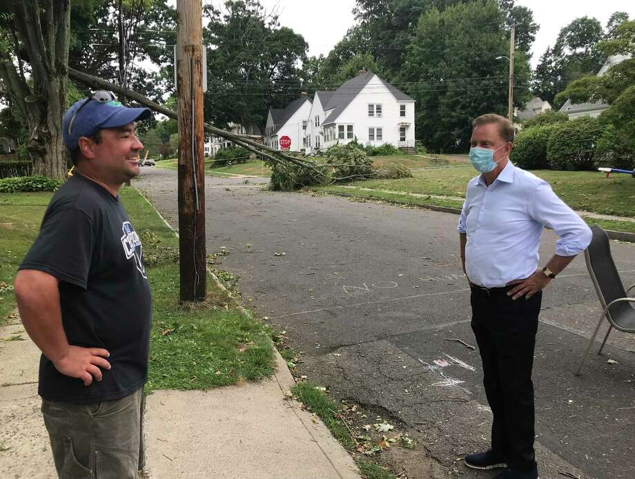 Gov. Ned Lamont talks with West Hartford resident Kerry Kato, left, on Whitman Ave. after the street was blocked by a fallen tree in storm Isaias. Also shown are adults and children cleaning up the street. Photo: Dan Haar /Hearst Connecticut Media