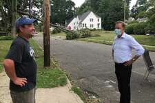 Gov. Ned Lamont talks with West Hartford resident Kerry Kato, left, on Whitman Ave. after the street was blocked by a fallen tree in storm Isaias. Also shown are adults and children cleaning up the street.