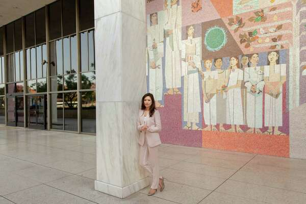"Jessica Denson, the Trump campaign's former Hispanic outreach director, stands in front of a mural by Richard Haines titled ""Celebration of our Homeland"" at the Federal Building in downtown Los Angeles."