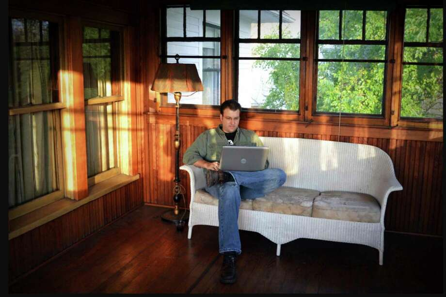 """Jeff Vande Zande of Midland sits in the upstairs screened porch of the Theodore Roethke house in Saginaw while writing """"American Poet."""" (Photo provided/Jeff Vande Zande)"""