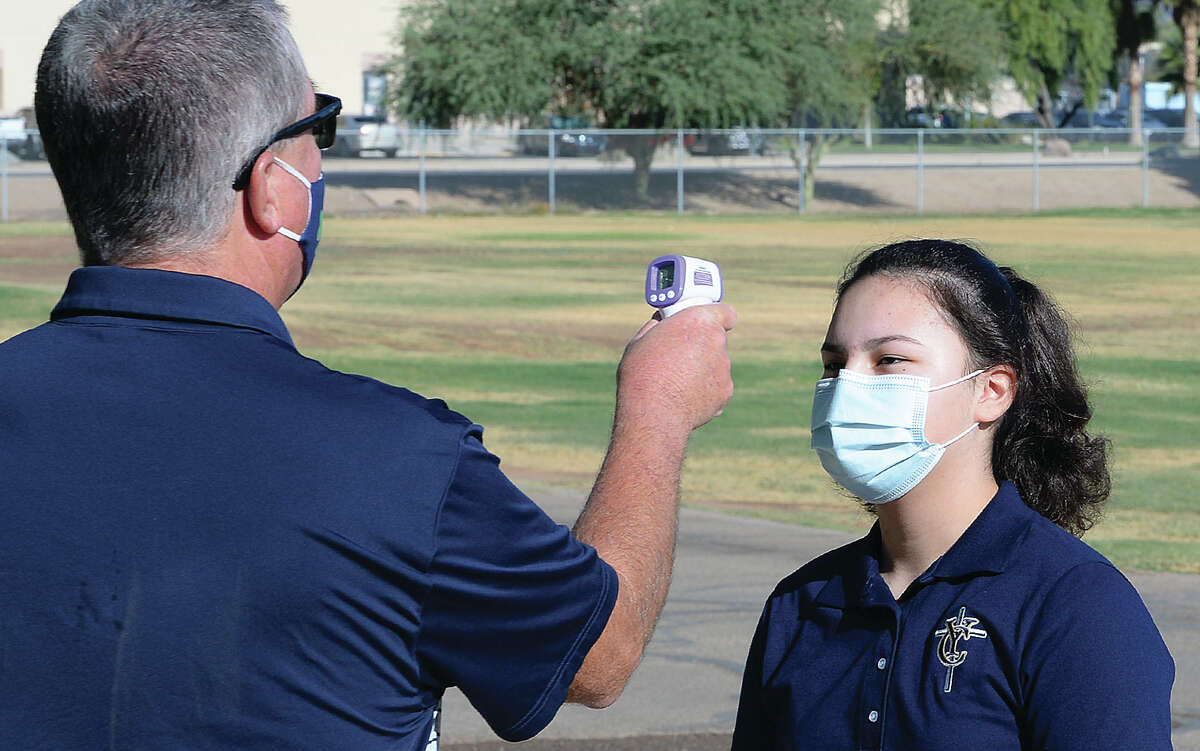 Yuma Catholic staff member Bobby McGalliard, left, checks the temperature of a student attending a freshman orientation session Thursday morning, Aug. 6, 2020, on the first day of school in Yuma, Ariz. Freshmen were divided into groups, using four classrooms for each orientation session.
