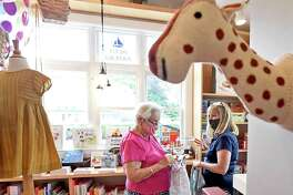 Customers Joan Muratori of New York, left, and Jeanne Lyons of Madison shop for a baby gift at the Just Hatched baby clothing and accessory store in Guilford. on Friday, July 31.