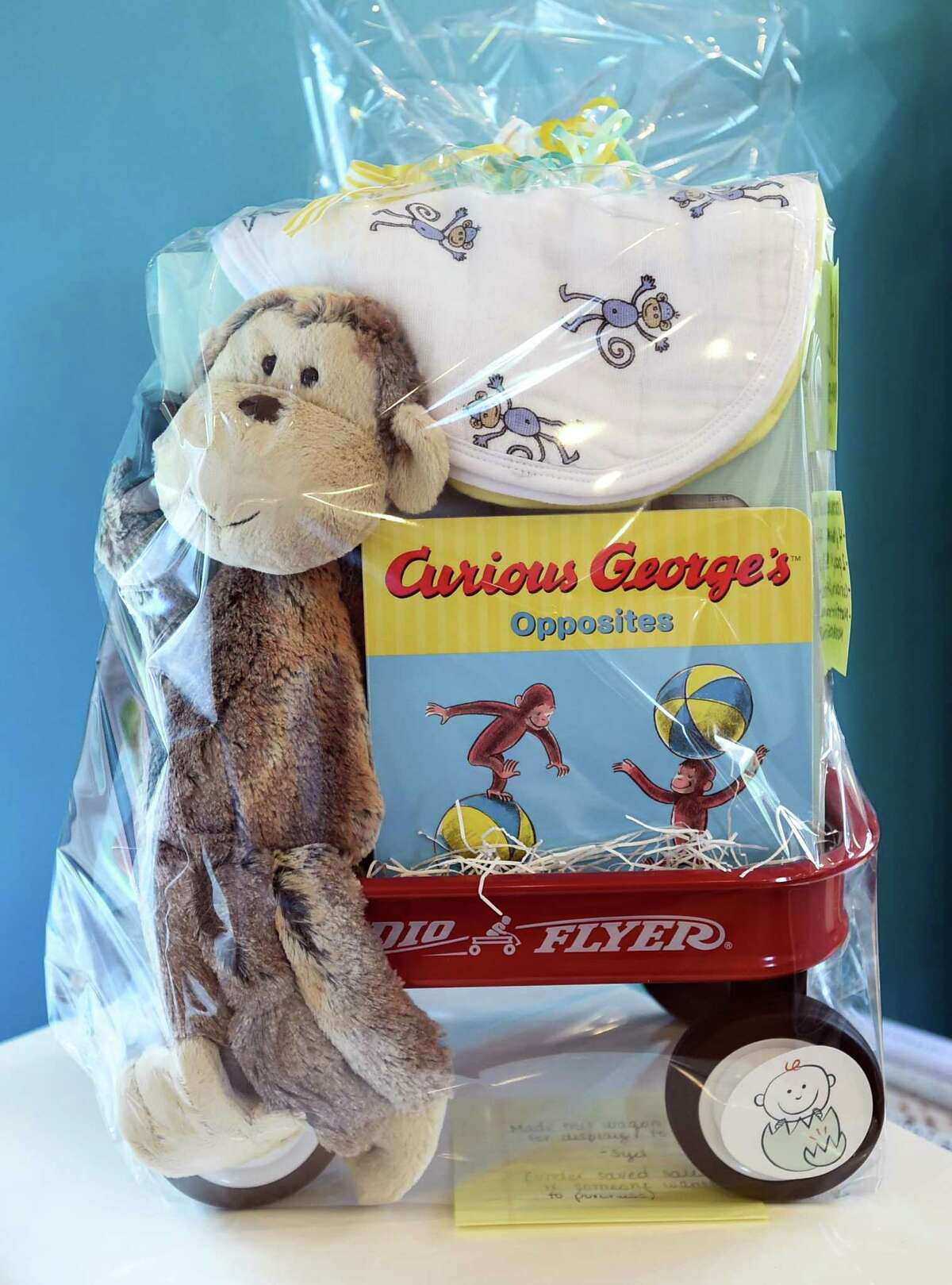 Guilford, Connecticut - Friday, July 31, 2020: A baby gift bundle of a 4-pack of swaddle, a 2-pack of bury tips, a Curious George and Mattie the Monkey stuffed animal at Just Hatched baby clothing and accessory store in Guilford.