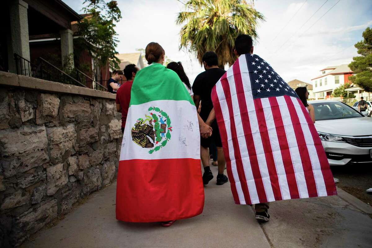 Samantha Ordaz, 20, and her boyfriend César Antonio Pacheco, 24, walk together representing the two neighboring nations, the United States States and Mexico during a walk against violence Sunday, Aug. 4, 2019, in El Paso. Both were born in El Paso, but parents and grandparents migrated to the United States.