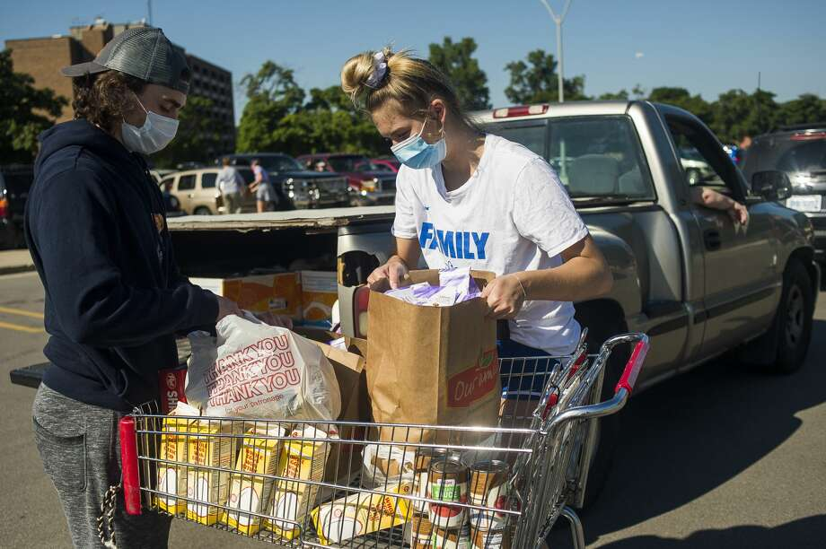 Volunteers Carter Thomas, left, and Anna Tuck, right, load groceries into a vehicle during a mobile food pantry hosted by the Midland County Emergency Food Pantry Network Friday, Aug. 7, 2020 at Midland High School. Another mobile pantry was held simultaneously at the Saginaw Bay Ice Arena. (Katy Kildee/kkildee@mdn.net) Photo: (Katy Kildee/kkildee@mdn.net)