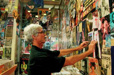 Bobby Barnard, of Sundance record store, helps post photograph on the wall as he slowly builds shrines for musicians at Sig's Lagoon, photographed in the first floor of Sig's Lagoon on Tuesday, Aug. 7, 2012, in Houston. Bobby Barnard was living in Houston when his best friend Sanford Randinsky was shot and killed in HPD raid. He left town and settled in San Marcos where he set up a record store called Sundance, which became one of the longest-running independent stores in Texas. Earlier this year he finally decided to close the store, despite having thousands of LP's. Tomas Escalante, former employee, offered his store Sig's Lagoon to open a Sundance annex. ( Mayra Beltran / Houston Chronicle )