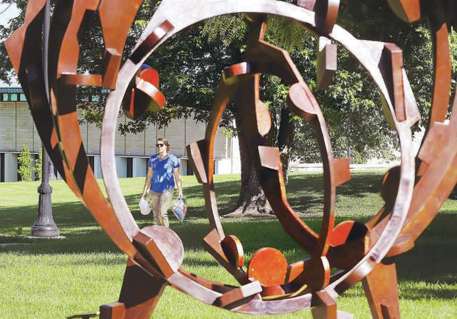 """In this June 2019 file photo, a woman walks across the Lewis and Clark Community College campus as seen through the 2010 bronze sculpture by artist Joel Perlman called """"Rolling on the River."""" The college is hosting a virtual recruitment event Tuesday. Photo: John Badman 