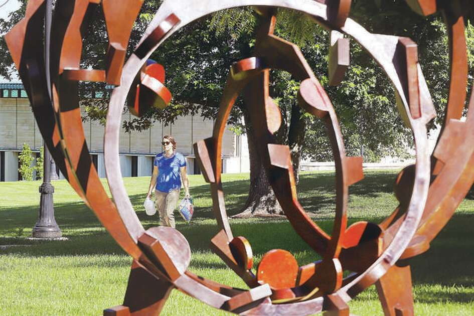 """In this June 2019 file photo, a woman walks across the Lewis and Clark Community College campus as seen through the 2010 bronze sculpture by artist Joel Perlman called """"Rolling on the River."""" The college is hosting a virtual recruitment event Tuesday."""