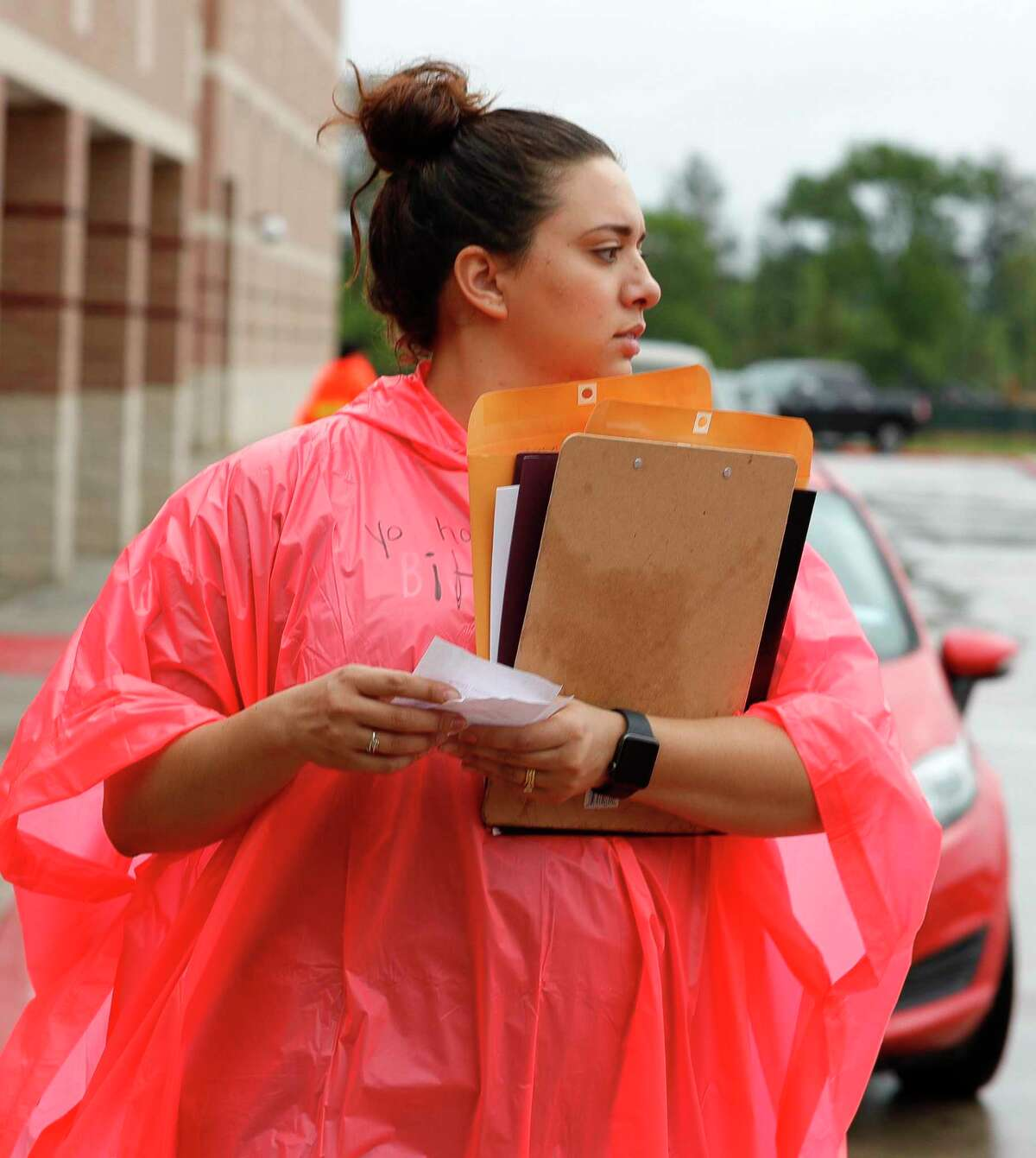 Itzel Lopez carries folders in the rain as teachers, faculty and staff distribute packets of schoolwork and supplies to students at Bozman Intermediate School, Friday, March 20, 2020, in Conroe. CISD will continue to work with families who have difficulty accessing the internet as the new school year starts to make sure students are getting an education.