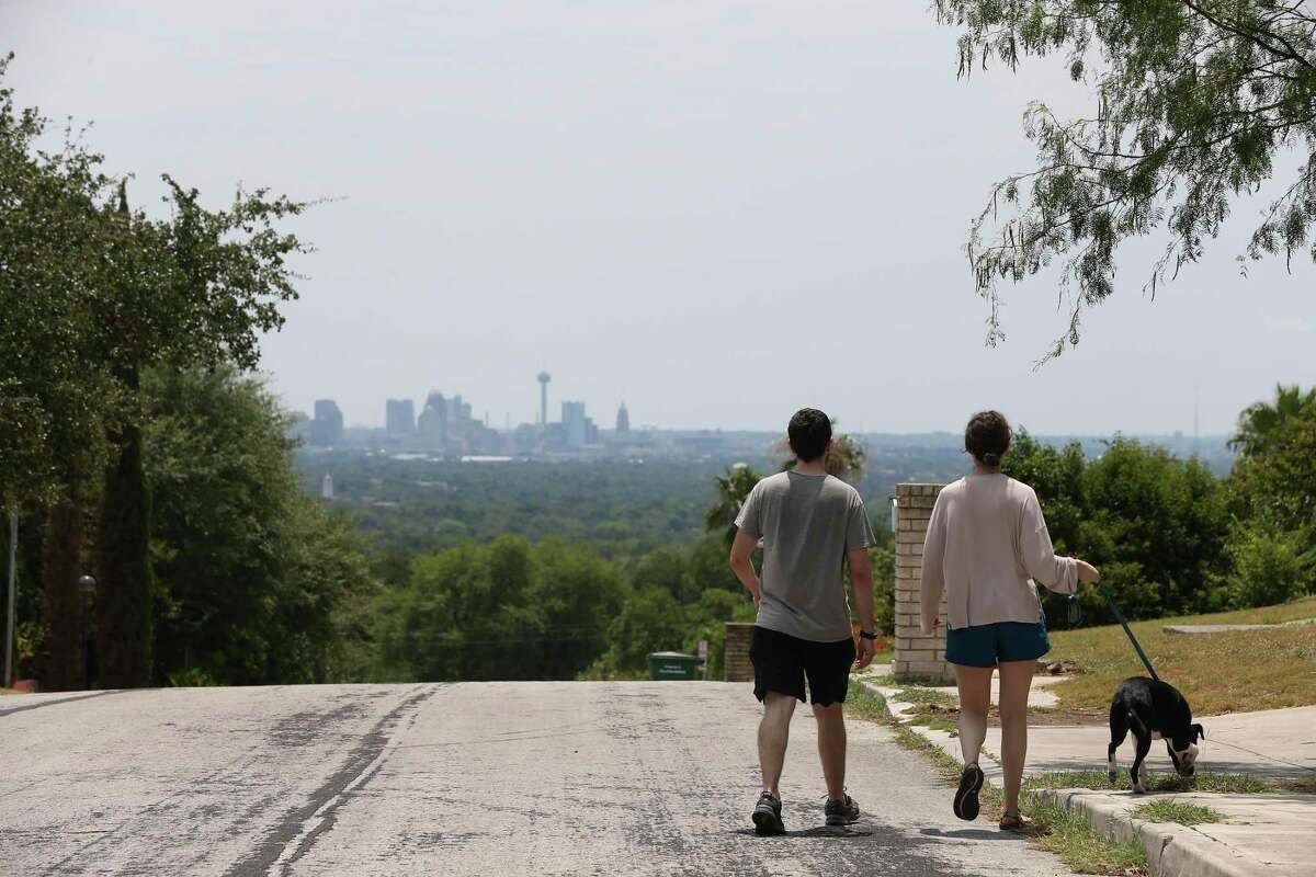 A couple walks their dog along Clubhill Drive. It is one of San Antonio's scenic drives people can enjoy without getting out of their air conditioned vehicles.