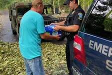 A police officer delivers water to a Newtown resident following Tuesday's devastating storm.