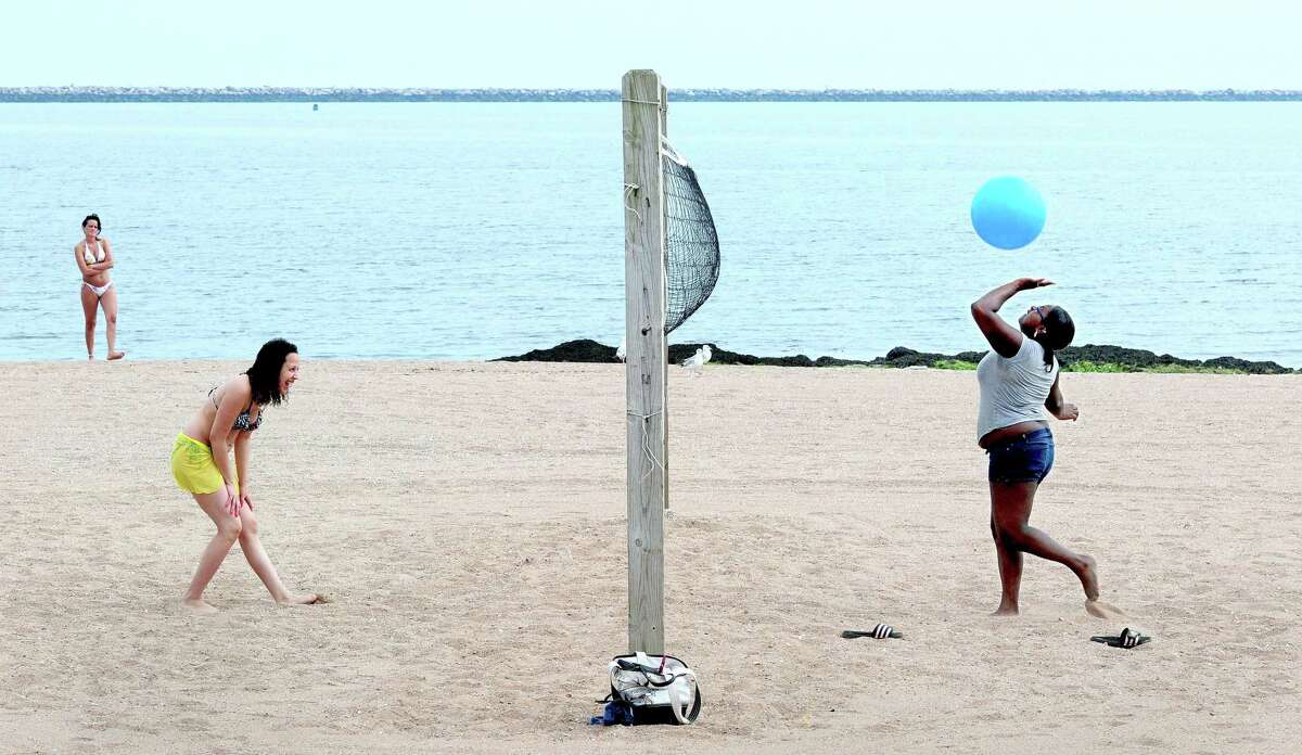 Two people enjoy a game of volleyball at Lighthouse Point Park in New Haven.